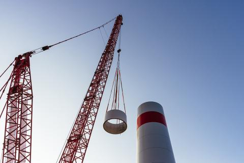 wind-turbine-construction-tower-crane-low-angle-clear-sky